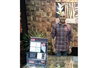 Serge with display of Renaza Wooden Wall Cladding and Luminosa light switch brochures